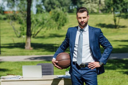 Photo pour Businessman standing neat table in park, holding basketball and looking at camera - image libre de droit