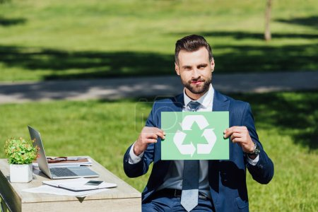 Photo pour Jeune homme d'affaires s'asseyant dans le stationnement près de la table avec l'ordinateur portatif, tenant la carte avec le signe de recyclage et regardant l'appareil-photo - image libre de droit