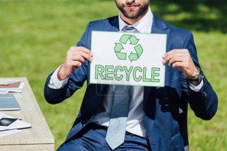 Photo pour Vue recadrée de l'homme d'affaires s'asseyant près de la table et affichant la carte avec le signe de recyclage - image libre de droit