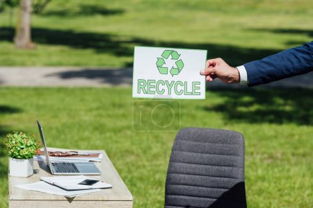cropped view of businessman holding card with recycle sign near table in park