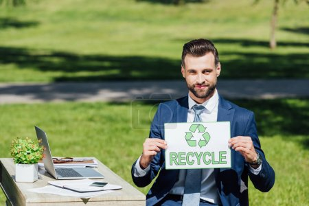 businessman sitting near table and showing card with recycle lettering