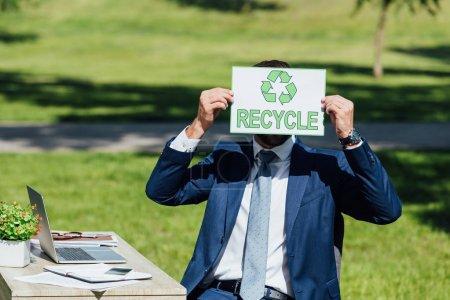 joven hombre de negocios sentado cerca de la mesa y cubriendo la cara con tarjeta con letras de reciclaje