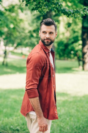 Photo for Young handsome man in red shirt looking away while standing in park - Royalty Free Image
