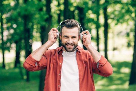 Photo pour Jeune homme beau regardant l'appareil-photo et mettant sur des écouteurs tout en restant dans le stationnement - image libre de droit