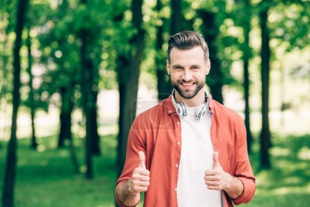 Foto de Young man in red shirt standing in park with headphones on neck and showing thumbs up - Imagen libre de derechos