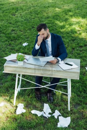 tired businessman sitting in park behind table with laptop, smartphone, notebooks and flowerpot with many crumpled sheets of paper on grass