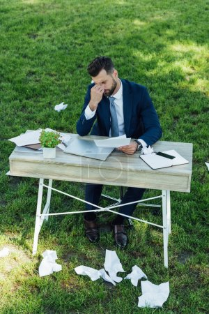 Foto de Tired businessman sitting in park behind table with laptop, smartphone, notebooks and flowerpot with many crumpled sheets of paper on grass - Imagen libre de derechos