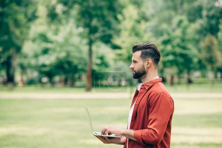 Photo for Side view of young man standing in park with laptop in hands and looking away - Royalty Free Image