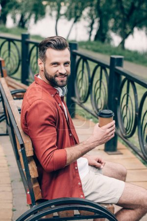 Photo for Young man in red shirt sitting on bench, holding coffee to go, smiling and looking at camera - Royalty Free Image