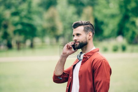 Photo for Young man standing in park and talking on smartphone - Royalty Free Image