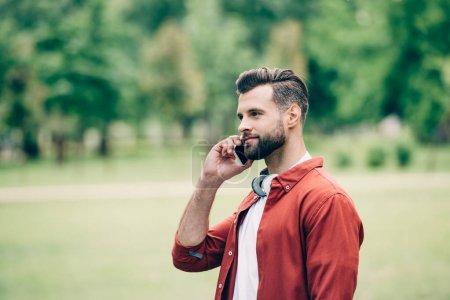 Photo pour Jeune homme debout dans le parc et parler sur smartphone - image libre de droit