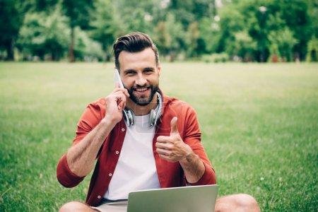 Photo pour Jeune homme assis sur l'herbe avec ordinateur portable, parlant sur smartphone et montrant pouce vers le haut - image libre de droit