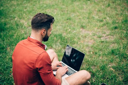 Photo for Back view of man sitting on grass and using laptop - Royalty Free Image