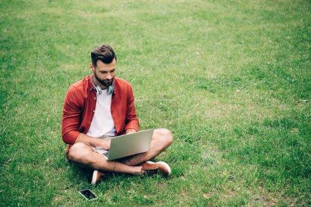 Photo pour Man sitting on grass in park near smartphone and using laptop - image libre de droit