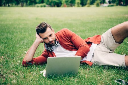Photo for Young man lying on grass in park and using laptop - Royalty Free Image