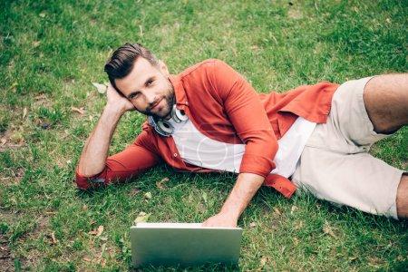 Photo pour Jeune homme se trouvant sur l'herbe dans le stationnement, utilisant l'ordinateur portatif et regardant l'appareil-photo - image libre de droit