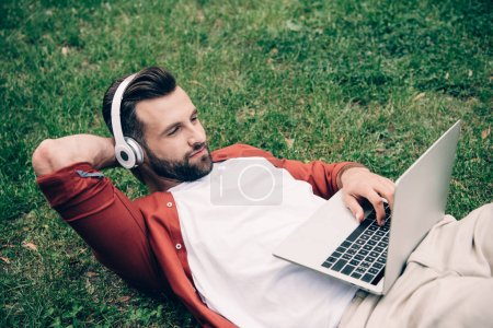 Photo for Young man lying on grass in park, using laptop and listening to music on headphones - Royalty Free Image
