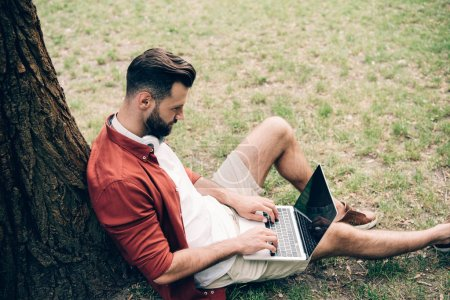 Photo for Side view of young man sitting on grass near tree and using laptop - Royalty Free Image