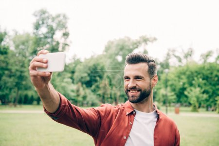 Photo for Handsome man standing in park, smiling and taking selfie - Royalty Free Image
