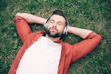 Photo pour Jeune homme avec les yeux fermés se trouvant sur l'herbe avec des mains derrière la tête et écoutant la musique - image libre de droit