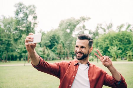 Photo pour Handsome man standing in park, smiling, taking selfie and showing victory sign - image libre de droit