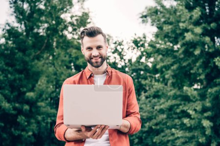 Photo pour Young man standing in park, holding laptop and looking at camera - image libre de droit