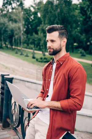 Photo for Young man using laptop near park and looking away - Royalty Free Image