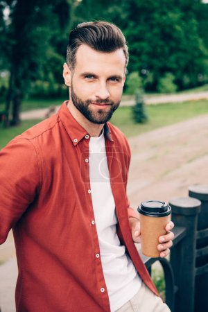 Photo for Handsome young man holding coffee to go and looking at camera - Royalty Free Image