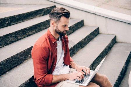 Photo pour Jeune homme utilisant l'ordinateur portatif tout en s'asseyant sur des escaliers en pierre - image libre de droit