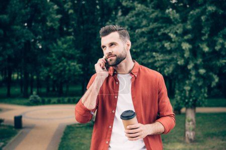 young man talking on smartphone and holding coffee to go while standing in park