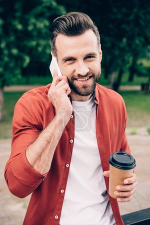 Photo for Handsome man talking on smartphone, holding coffee to go and looking at camera while standing in park - Royalty Free Image
