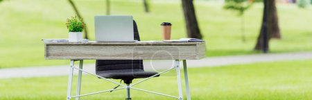 Photo for Panoramic shot of white office table with laptop, coffee to go and flowerpot in park - Royalty Free Image