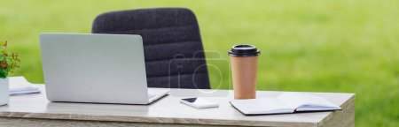 Foto de Panoramic shot of table with laptop, smartphone, notebook and coffee to go near office chair in park - Imagen libre de derechos