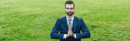Photo pour Panoramic shot of young man meditating with closed eyes while standing in park - image libre de droit