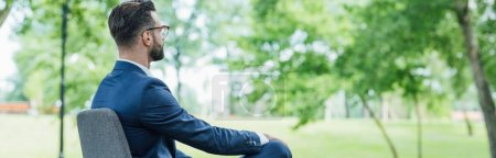 Photo for Panoramic shot of young man sitting in office chair and looking away - Royalty Free Image