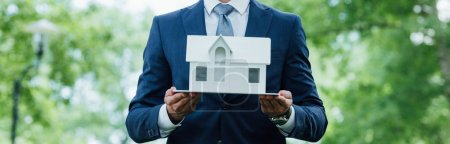 Photo for Panoramic shot of young businessman holding house layout while standing in park - Royalty Free Image