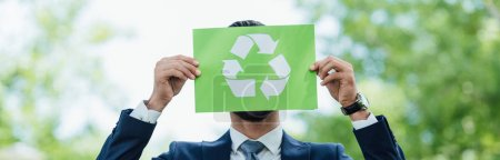 Foto de Panoramic shot of businessman holding card with recycle sign while standing in park - Imagen libre de derechos