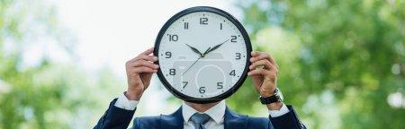 plan panoramique de l'homme d'affaires couvrant le visage avec horloge tout en se tenant dans le parc