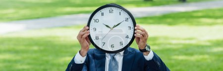 panoramic shot of businessman covering face with clock while standing in park