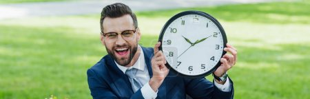 Photo for Panoramic shot of businessman looking at camera, smiling and presenting clock - Royalty Free Image