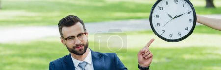 panoramic shot of businessman pointing with finger at clock while sitting in park