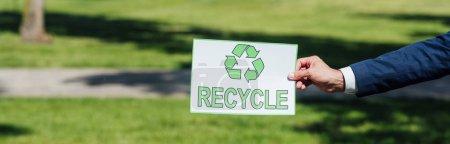 Photo pour Plan panoramique de l'homme tenant la carte avec panneau de recyclage tout en se tenant dans le parc - image libre de droit