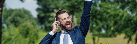 Photo pour Tir panoramique de jeune homme d'affaires excité écoutant la musique et levant la main dans l'air - image libre de droit
