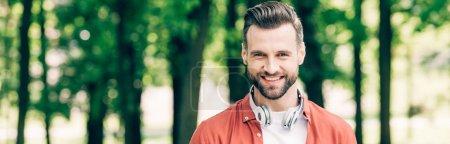 Photo pour Tir panoramique de l'homme avec le sourire d'écouteur et regardant l'appareil-photo - image libre de droit