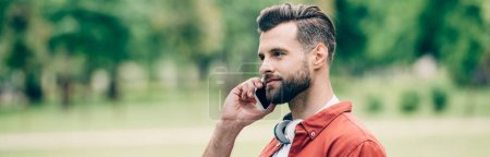 Photo for Panoramic shot of man talking on smartphone while standing in park - Royalty Free Image