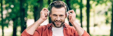 Photo pour Tir panoramique de l'homme mettant des écouteurs sur la tête, souriant et regardant l'appareil-photo - image libre de droit