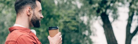 Photo for Panoramic shot of man holding coffee to go and looking away - Royalty Free Image