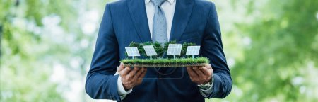 Photo pour Panoramic shot of businessman holding sun batteries layout while standing in park - image libre de droit