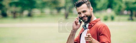 Photo pour Prise de vue panoramique de l'homme parlant sur smartphone, souriant, pointant du doigt et regardant la caméra - image libre de droit