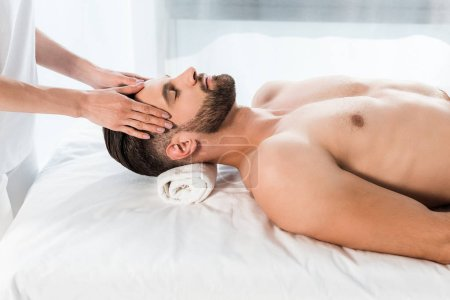 Photo for Cropped view of young woman doing massage to handsome man with closed eyes - Royalty Free Image